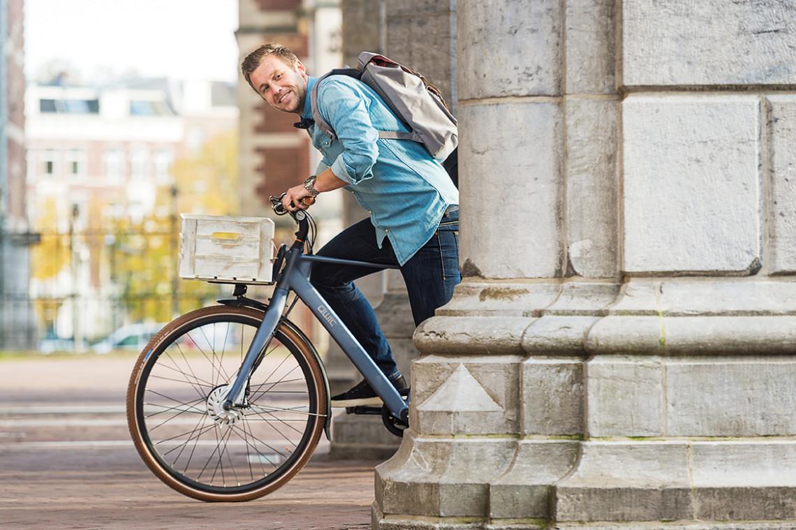 QWIC nieuwsbrief aanmelding. Man op de Premium FN7.1 urban rijdt op fiets en kijkt om hoekje